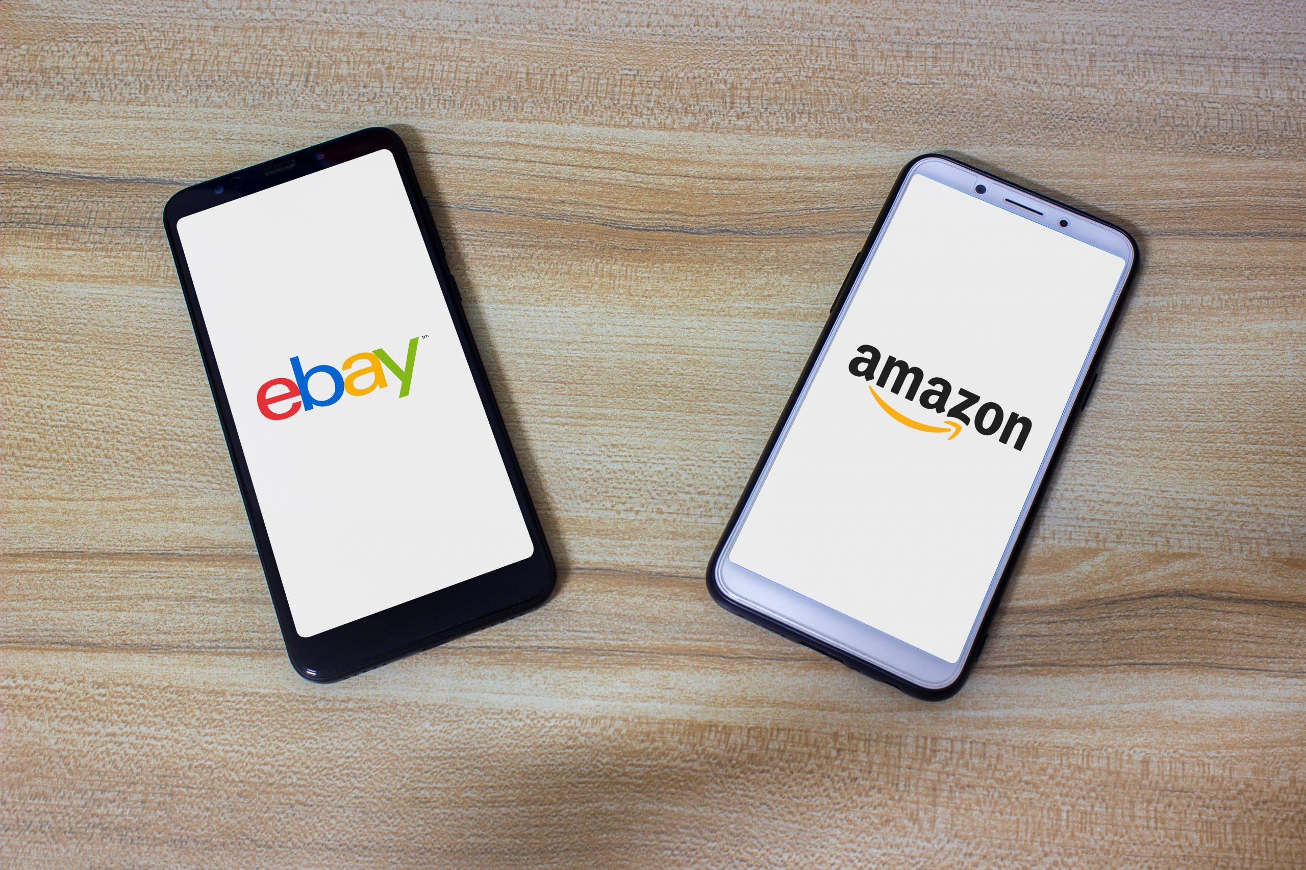 eBay and amazon logos on two smartphones on a table