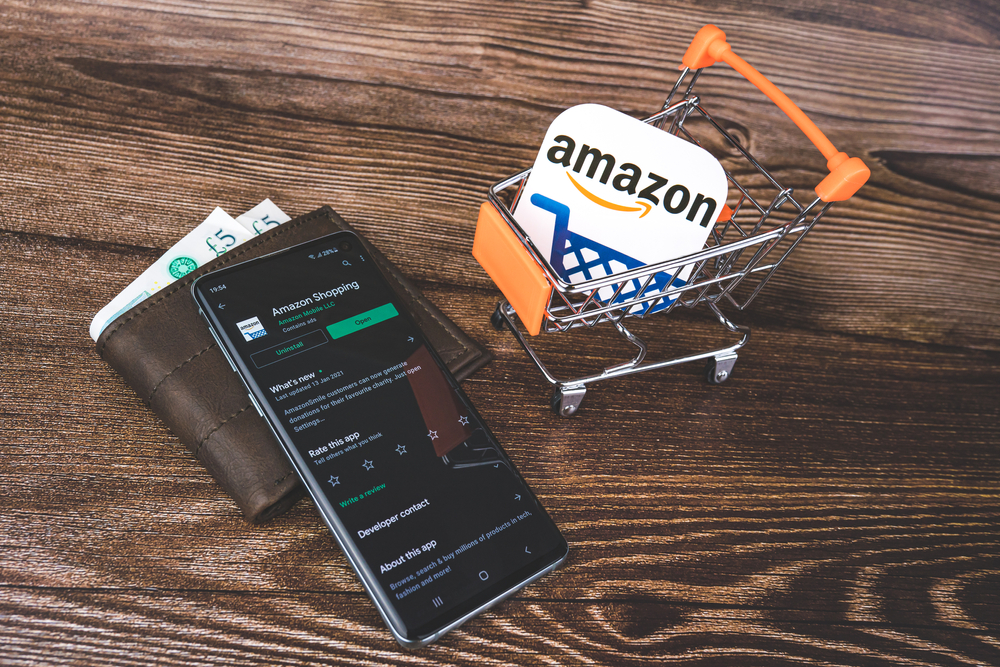 Mini shopping trolley with Amazon logo and Amazon app on Google Play on smartphone and wallet with pounds currency.