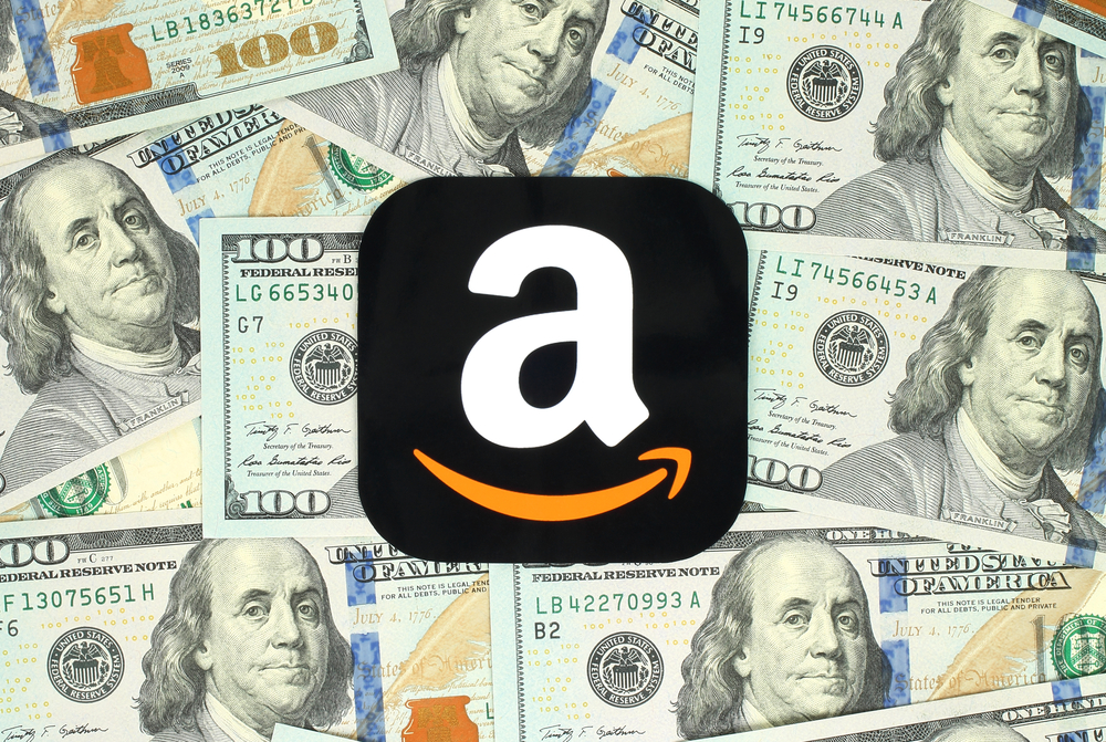 Amazon icon printed on paper and placed on money background.