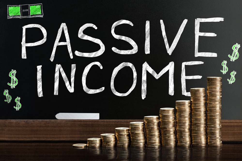 Passive Income Word On Blackboard Behind Stacked Coins